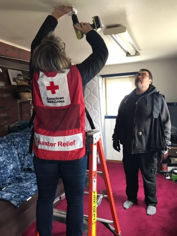 Suzanne installing an alarm in Kaktovik with Chief Brower